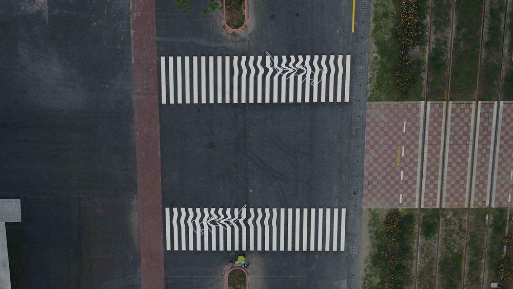 Faixas de pedestres borradas como se fossem feitas de fios.