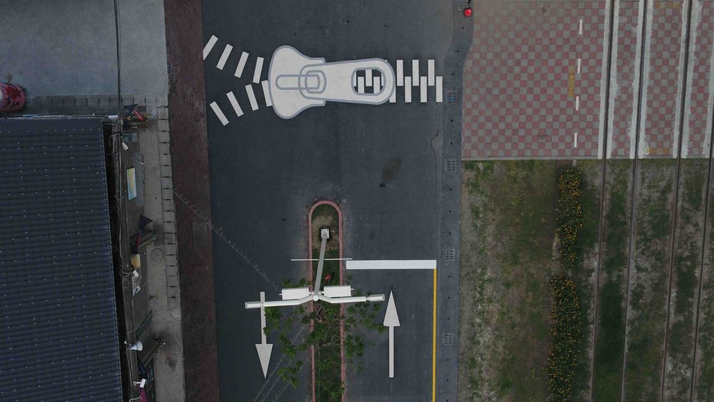 Um ziper pintado sobre uma faixa de pedestres.