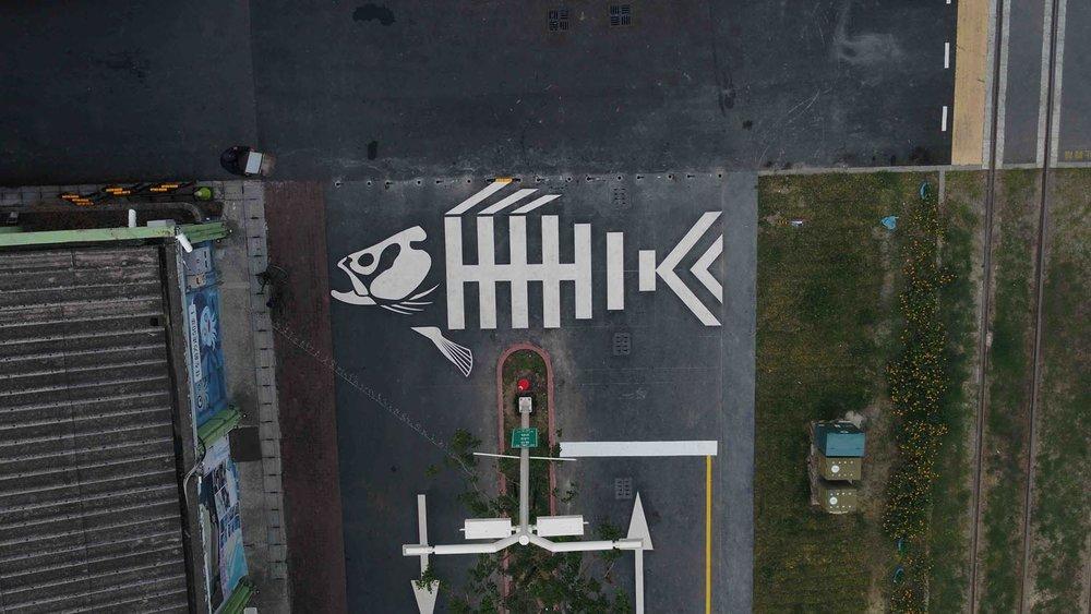 Esqueleto de peixe pintado sobre uma faixa de pedestres.