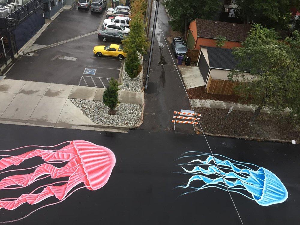 Foto de águas vivas coloridas pintadas no asfalto.