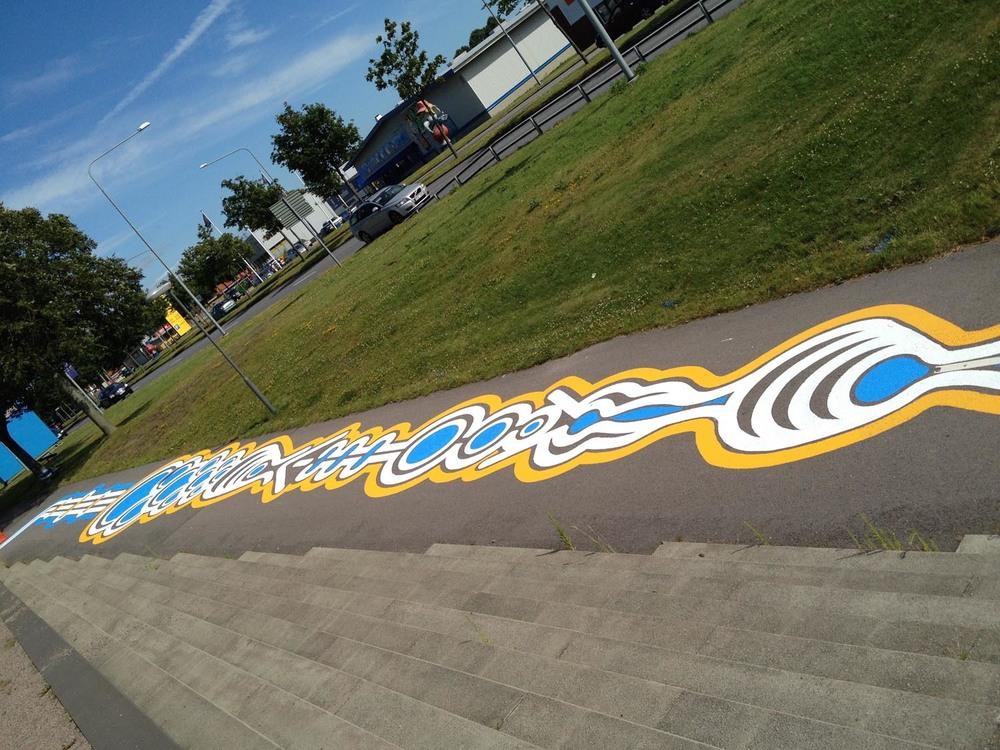 Formas geométricas coloridas pintadas sobre a rua e passarelas.